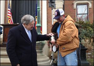 Iowa Gov. Terry Branstad, left, pardons a Berkshire pig named Bonnie, held by her owner Randy Hilleman.