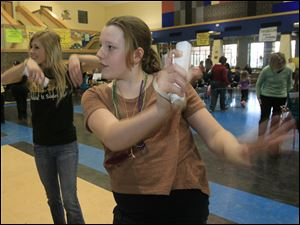 Kayla Pietkowski, 17, a senior, left, and Julia Lee, 11, a sixth-grader from Perrysburg dance to