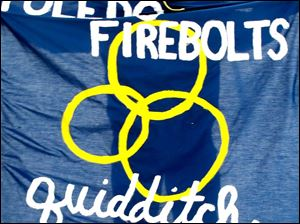Alex Scheer unfurls the Toledo Firebolts  Quidditch team flag during The Glass City Quidditch Classic.