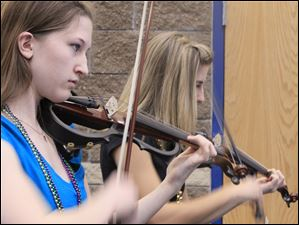 Perrysburg High School's Rock Orchestra violinists Madison Humphrey, 15, a sophomore, left, and Sydney Kieo, 18, a senior, in performance at Mardi Gras.