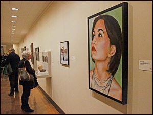 Visitors take in works by local artists Friday evening during the 94th Toledo Area Artists Exhibition.