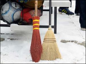 Two different types of broomsicks for the match rest against a team's bench during The Glass City Quidditch Classic.