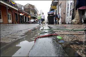 Beads and trinkets litter the 400 block of  Bourbon Street in the French Quarter on Sunday. New Orleans police said Saturday's shooting did not prevent people from returning Sunday night to continue to party.