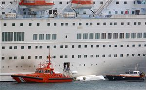 An orange rescue boat docks by a capsized lifeboat from the British-operated cruise ship Thomson Majesty in Santa Cruz port of the Canary Island of La Palma, Spain, today.