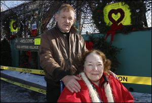 Larry and Susan Ocheske pose in front of a Sandy Hook memorial they arranged at the Old Amtrack Village site at the corner of Emerald and Logan streets in Toledo. They also provided two large Valentine cards for people to sign across the street from the memorial.