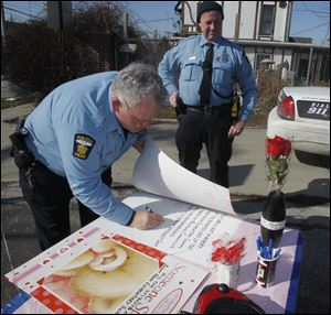 Toledo Police officers Mike Stewart, left, and Craig Smith sign cards for Sandy Hook Elementary students.