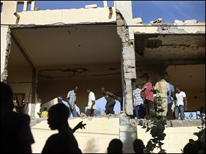 Malian people mill through the heavily shelled police station in Gao, northern Mali, Monday, one day after Mujao fighters engaged in a firefight with Malian forces.