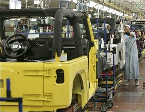 Vera Coleman installs parts in a Jeep Wrangler at Chrysler's Toledo Assembly Complex in Toledo.