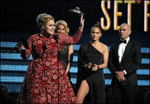"Adele, left, accepts the award for best pop solo performance for ""Set Fire to the Rain"" at the Grammy Awards on Sunday in Los Angeles. Looking on from right are presenters Pitbull and Jennifer Lopez."