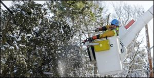 Andrew Varney, a lineman from Canton, N.Y., frees a pine tree stuck in lines in Scituate, Mass. Crews raced to restore power to more than 220,000 people.