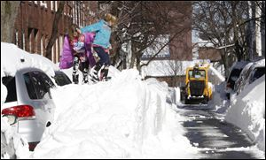 Riley Clark, left, and her sister Mckenzie play on top of a pile of snow as a snow removal machine clears a path in Boston. The city recorded 24.9 inches of snow, its fifth-largest snowstorm on record.