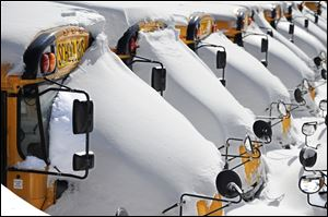 Idle school buses remain snow-covered in Hartford on Sunday. Many districts in the region closed the schools as the area continues to dig out from the massive winter storm.