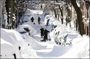 People pause while digging out their cars in Boston. Driving bans were lifted on Sunday and flights resumed at most airports. Boston's subway service was to resume partial service on Monday.