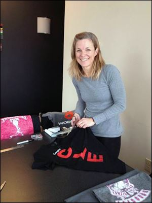 Beth White, a Crossfit trainer for Comet Crossfit, helps cut patches for the Joe Lengel tribute quilt.
