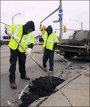 Ernest Persley, left, and Marvin Arnold, both of Toledo, working on a pothole on Phillips at Haverhill.