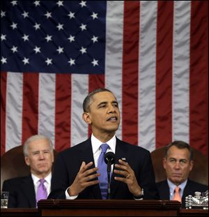 President Barack Obama, flanked by Vice President Joe Biden and House Speaker John Boehner of Ohio, gestures as he gives his State of the Union address during a joint session of Congress on Capitol Hill in Washington.
