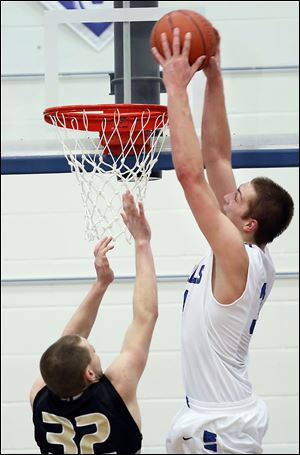 Anthony Wayne's Mark Donnal, right, dunks over Perrysburg's Chris Schimmoeller. Donnal finished with 13 points, 13 rebounds, and six blocked shots.