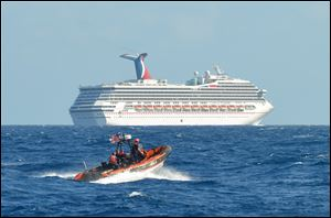 A small boat belonging to the Coast Guard Cutter Vigorous patrols near the cruise ship Carnival Triumph in the Gulf of Mexico, Monday.