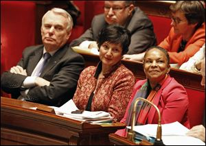 French justice minister Christiane Taubira, right, sits on the government bench with social affairs minister Dominique Bertinotti, center, and prime minister Jean Marc Ayrault, during the vote at the National Assembly in Paris of a new law legalizing gay marriage.