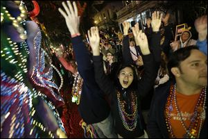 Revelers yell for beads and trinkets during the Krewe of Orpheus Mardi Gras parade in New Orleans, Monday.