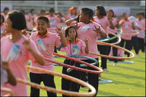 Participants perform in a hula hoop competition to break the Guinness World Record for most people dancing with hula hoops, at Thammasat University, Pathumthani, Thailand  Tuesday.