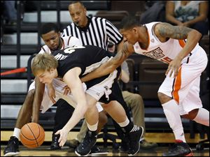 Bowling Green State University guard Chauncey Orr (21) and forward A'uston Calhoun (15) defend against  Western Michigan forward Connor Tava (2).