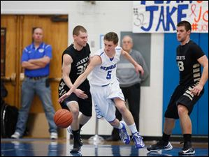 Anthony Wayne's Hunter Debo (5) drives past  Perrysburg's  Chris Schimmoeller (32).