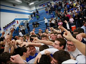Anthony Wayne's Matt Fox (3), left, celebrates with fans after defeating Perrysburg 54-48.