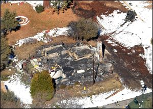 In this aerial photo, law enforcement authorities investigate the burnt-out cabin today where accused quadruple-murder suspect Christopher Dorner was believed to have died after barricading himself inside, during a Tuesday stand-off with police in the Angeles Oaks area of Big Bear, Calif.