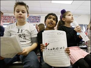 Second grade students Anthony Kovacs, 8, left, Nikhil Methi, 6, center, and Adrianna magers, 8, right, held autobiographies with ideas about ways they could help people in their communities.