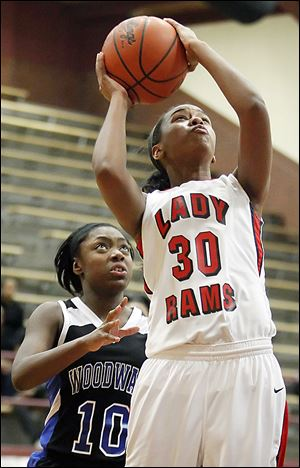 Rogers' Akienreh Johnson slips past Woodward's Asieonna Alfred on her way to the basket. Johnson and the rest of the Rams get a chance to defend their title on Saturday.