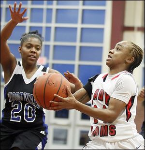 Rogers' Cha'Ron Sweeney goes to the basket against Woodward's Mylisha Fitchpatric during a City League semifinal at Scott High School. Sweeney led the Rams with 14 points despite spending a lot of time on the bench after Rogers built a big early lead against the Polar Bears.