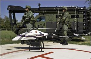 This photo provided by Vanguard Defense Industries, shows a ShadowHawk drone with Montgomery County, Texas, SWAT team members, September, 2011.