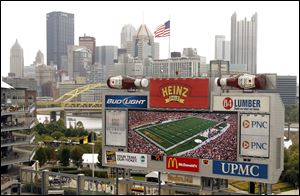 The Pittsburgh skyline looms behind the display screen at Heinz Field during an NFL football game between the Pittsburgh Steelers and the Atlanta Falcons. Billionaire Warren Buffett's Berkshire Hathaway and another investment group is acquiring the ketchup-fueled food conglomerate, H.J. Heinz Co.