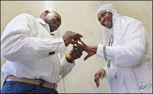 Larry Brown places a ring on the finger of his new bride, Floradeen Jackson Williams Brown, at the Lucas County Courthouse, on Valentine's Day.  The couple is from Southfield, Mich.