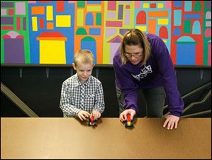 Fort Meigs fifth grade teacher Kelisa Boden gets set to race Lego cars with Grayson Scheub, 6, Thursday afternoon during class at Build It in Perrysburg. Opened on December 26 by Boden and her husband Bill, Built It teaches science using Legos and K'Nex.