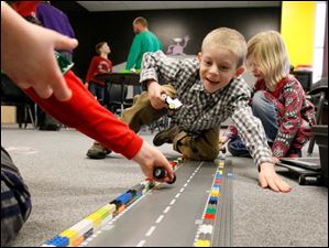Grayson Scheub, 6, center, cheers as he pits his Lego car against another child's during a demolition derby Thursday afternoon during class at Build It in Perrysburg. Opened on December 26 by Fort Meigs fifth grade teacher Kelisa Boden and her husband Bill, Built It teaches science with Legos and K'Nex. Classes run for one hour, twice a day Monday through Thursday. Each class costs $8. Build It also runs preschool sessions Tuesday and Wednesday from 9 a.m. until noon as well as open play for $5 an hour Thursday and Friday at that same time. Each week features a different lesson. On February 14 the class built cars and measured their speed, accuracy and durability.