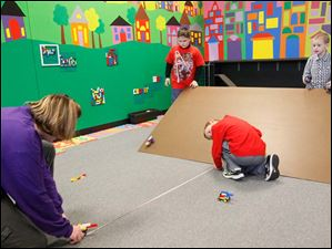 Kelisa Boden, left, and her son Andrew, 7, center, measure the distance his Lego car traveled down a homemade ramp Thursday afternoon during class at Build It in Perrysburg. Opened on December 26 by Fort Meigs fifth grade teacher Kelisa Boden and her husband Bill, Built It teaches science with Legos and K'Nex. Classes run for one hour, twice a day Monday through Thursday. Each class costs $8. Build It also runs preschool sessions Tuesday and Wednesday from 9 a.m. until noon as well as open play for $5 an hour Thursday and Friday at that same time.