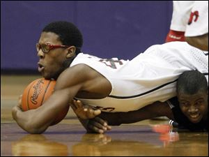 Rogers High School player Alejandro Williams, 44, dives over Start High School player Dion Ivery, 3, for a loose ball.