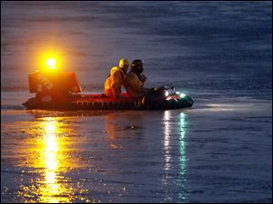 A rescue crew takes a hover craft into icy water to rescue the dogs.