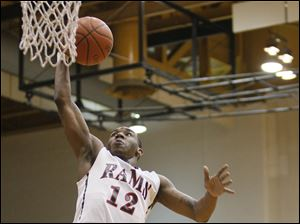 Rogers High School player Clemmye Owens V, 12, goes up for the dunk.