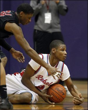 Bowsher's Aundre Kizer goes to the floor against Scott's Jermul Richardson. Kizer led the Rebels with 24 points.