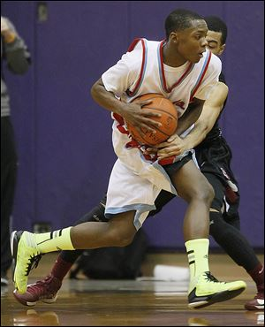 Bowsher's Dajuan King tries to get past Scott's Chris Harris in Friday night's City League semifinal at Waite's fieldhouse.
