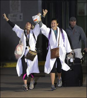 Kendall Jenkins, left, of Houston, celebrates with a friend after getting off the Carnival Triumph on Thursday night in Mobile, Ala.