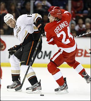 The Ducks' Ryan Getzlaf (15) is knocked off the puck by the Red Wings' Damien Brunner during the first period.