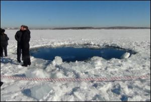 A circular hole in the ice of Chebarkul Lake where a meteor reportedly struck the lake near Chelyabinsk, about 930 miles east of Moscow,  Russia.