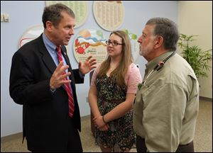 U.S. Sen. Sherrod Brown talks with Rachel Burns, a 15-year-old Springfield High School student and cystic fibrosis patient, and Dr. Pierre Vauthy, Director of Pedicatric Pulmonary Medicine at Toledo Children's Hospital, following a news conference at Toledo Children's Hospital.