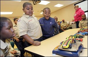 Fifth grader Jadan Turner, left, and third graders Donavan Linzy and Zarnell Dicus marvel as Donavan's pinewood derby car weighs in close to the maximum allowance during Boy Scouts at Glenwood Elementary School on Friday.