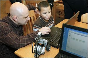Todd Beavers, educational technology teacher, helps first grader Alex Brown program a Lego robot during Lego Club at Glenwood Elementary School.
