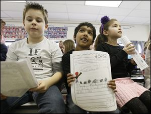 Second-graders Anthony Kovacs, 8, left, Nikhil Methi, 6, and Adrianna Magers, 8, hold papers with ideas about ways they could help people in their communities as they listen to a presentation at Woodland Elementary.by Robin Laird, Hannah's Socks board member and assistant principal at the junior high.